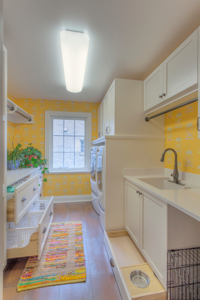 Inspiration for a large timeless galley ceramic tile dedicated laundry room remodel in Other with yellow walls, an undermount sink, white cabinets, quartz countertops, a side-by-side washer/dryer and recessed-panel cabinets
