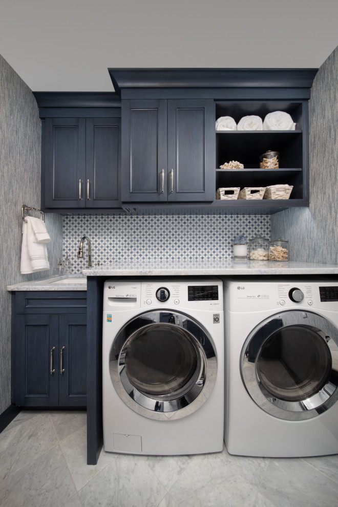 Example of a small transitional galley wallpaper, marble floor and white floor dedicated laundry room design in Other with blue cabinets, a side-by-side washer/dryer, gray countertops, a drop-in sink, beaded inset cabinets, marble countertops, multicolored backsplash, porcelain backsplash and blue walls