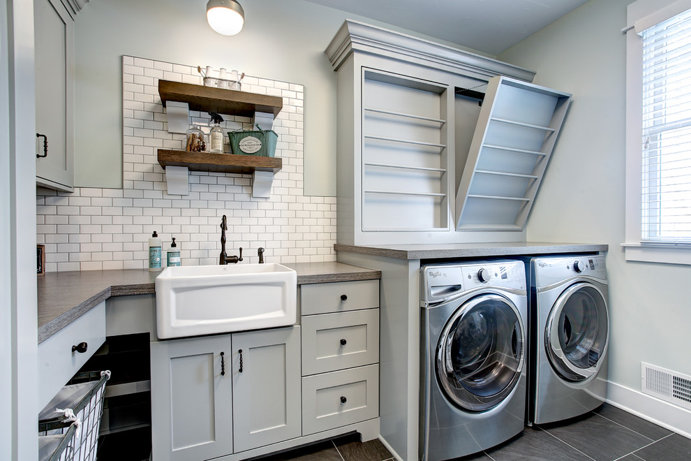 Inspiration for a transitional l-shaped gray floor dedicated laundry room remodel in Grand Rapids with a farmhouse sink, shaker cabinets, gray cabinets, gray walls, a side-by-side washer/dryer and gray countertops