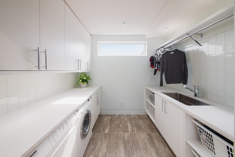 Example of a trendy galley gray floor dedicated laundry room design in Ottawa with an undermount sink, white walls, a side-by-side washer/dryer and white cabinets