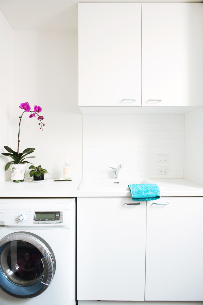 Inspiration for a large contemporary single-wall ceramic tile utility room remodel in Melbourne with a single-bowl sink, flat-panel cabinets, white cabinets, quartz countertops, white walls, a side-by-side washer/dryer and white countertops