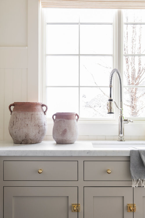 Dedicated laundry room - large coastal u-shaped dedicated laundry room idea in Salt Lake City with marble countertops, white walls, a side-by-side washer/dryer and multicolored countertops