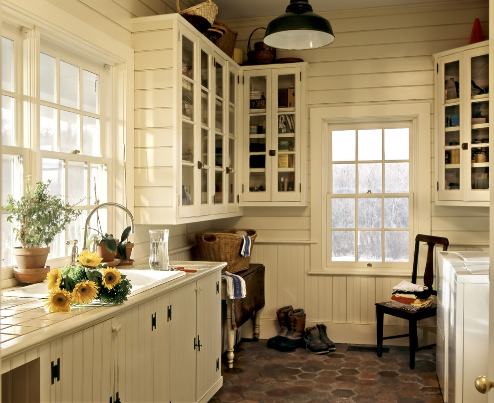 Inspiration for a farmhouse utility room remodel in New York with a drop-in sink, glass-front cabinets, white cabinets, tile countertops, white walls and a side-by-side washer/dryer