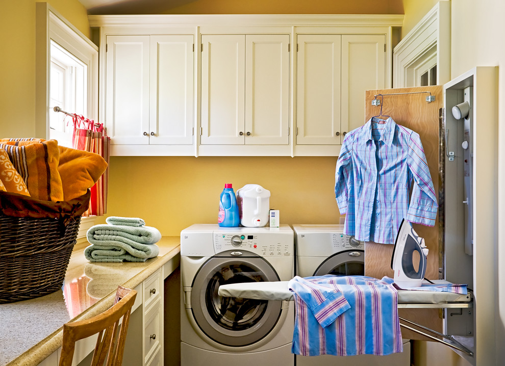 Elegant laundry room photo in New York with white cabinets
