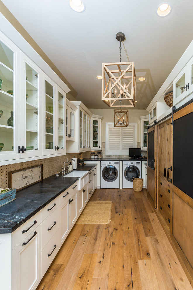Example of a large cottage u-shaped medium tone wood floor and brown floor laundry room design in Other with a farmhouse sink, shaker cabinets, white cabinets, soapstone countertops, beige walls, a side-by-side washer/dryer and black countertops