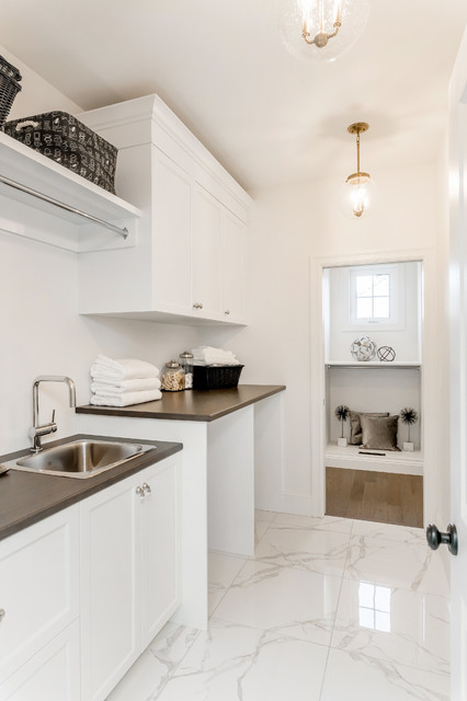 Inspiration for a small classic single-wall separated utility room in Other with a built-in sink, shaker cabinets, white cabinets, laminate countertops, white walls, marble flooring, a side by side washer and dryer and white floors.
