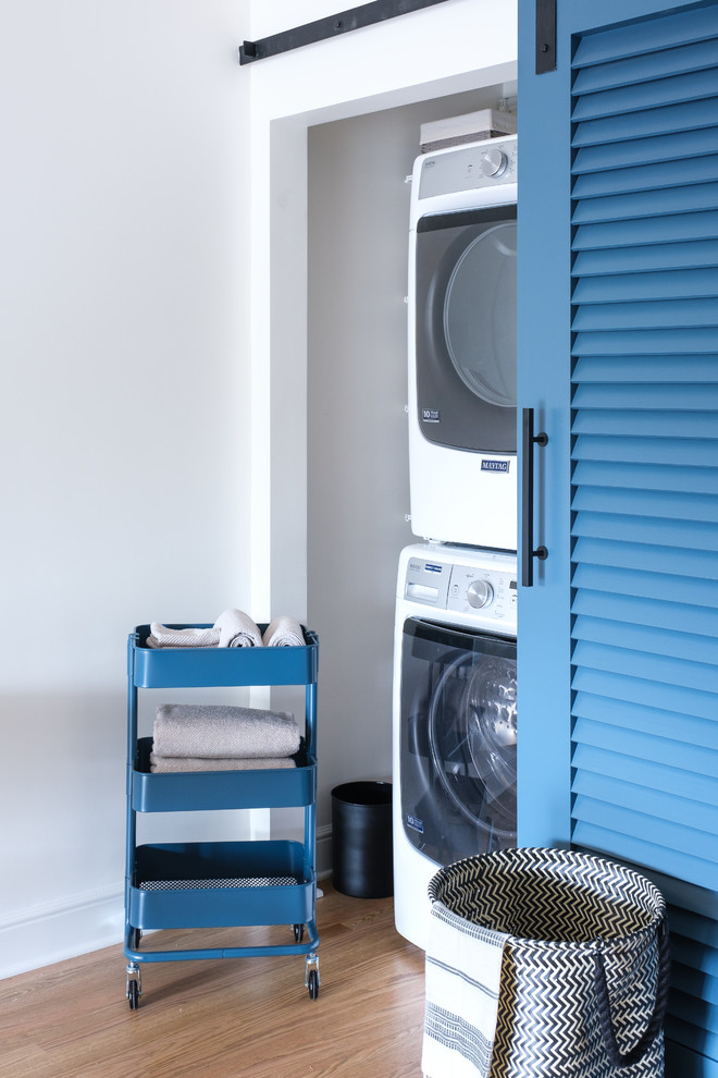 Example of a transitional medium tone wood floor and brown floor laundry closet design in San Francisco with a stacked washer/dryer and white walls