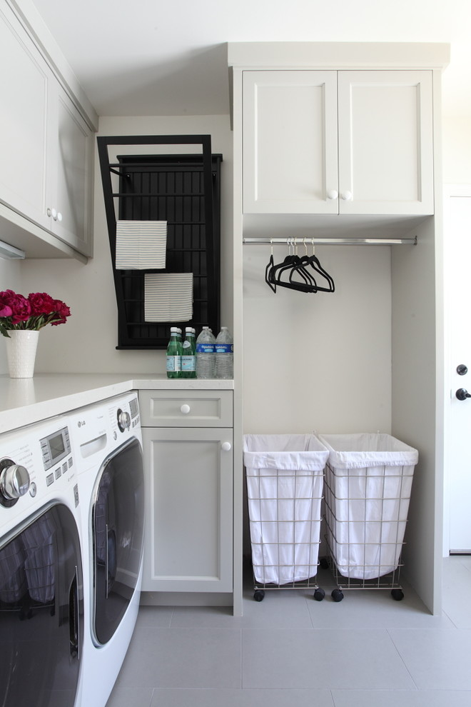 Example of a classic l-shaped laundry room design in Los Angeles with gray cabinets, recessed-panel cabinets, a side-by-side washer/dryer and white countertops