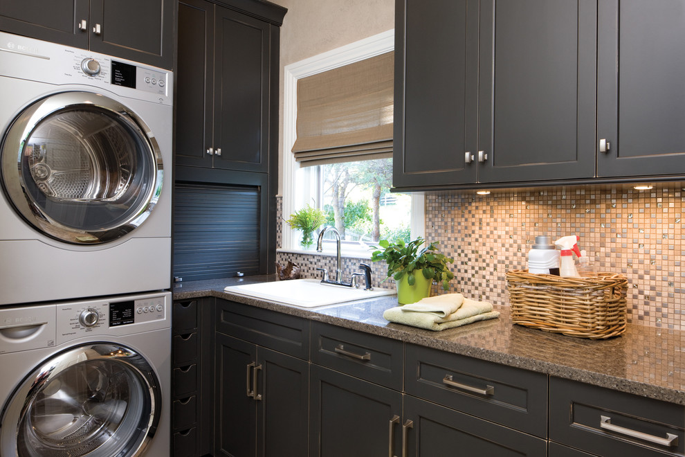 Elegant l-shaped laundry room photo in Minneapolis with black cabinets, a stacked washer/dryer, granite countertops, beige walls and shaker cabinets