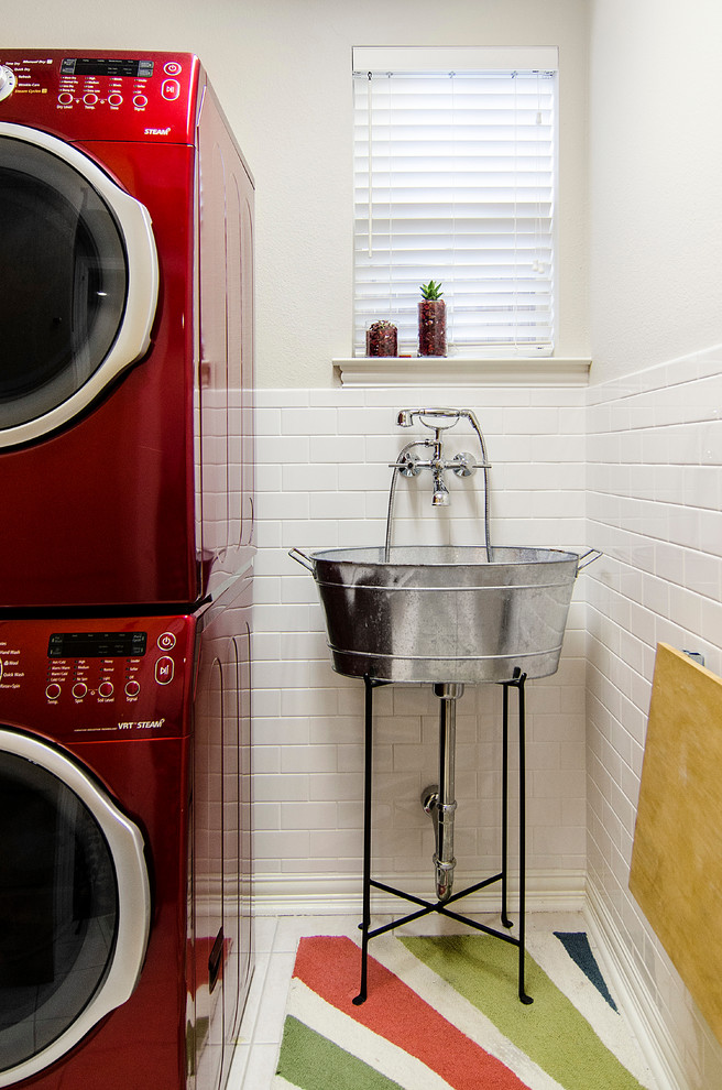 Inspiration for a timeless ceramic tile and white floor laundry room remodel in Dallas with an utility sink, a stacked washer/dryer and white walls