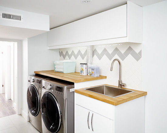 ... with Wood Countertops, White Walls and a Side-by-Side Washer and Dryer