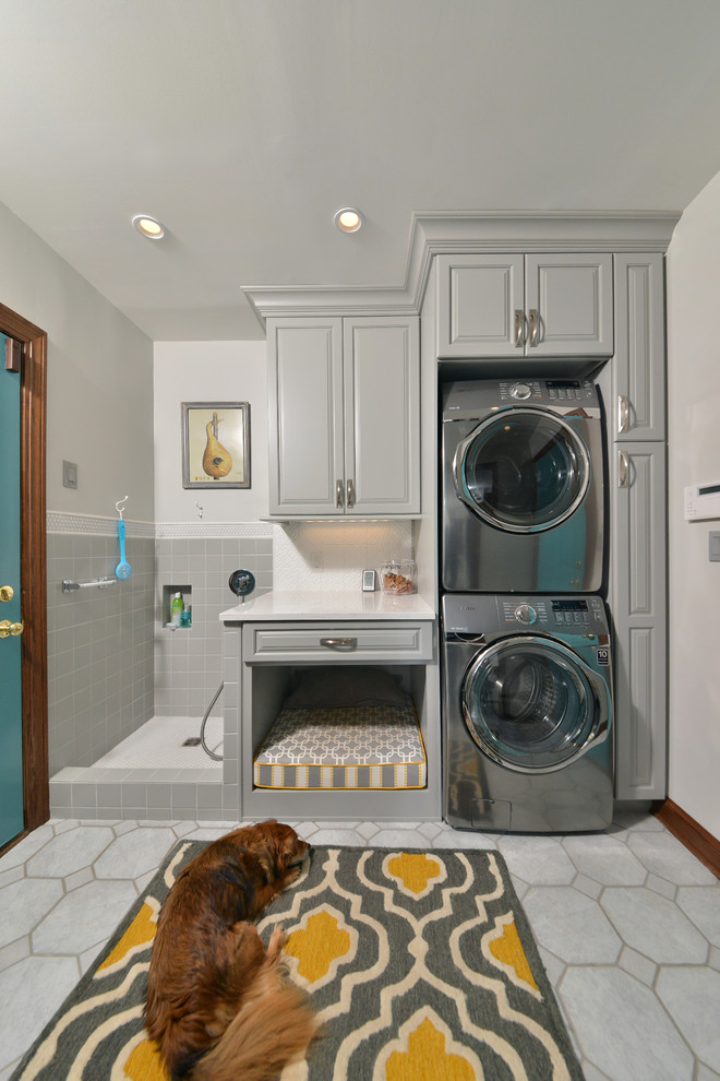Mid-sized elegant single-wall porcelain floor and gray floor utility room photo in Cleveland with an utility sink, raised-panel cabinets, gray cabinets, quartz countertops, gray walls and a stacked washer/dryer