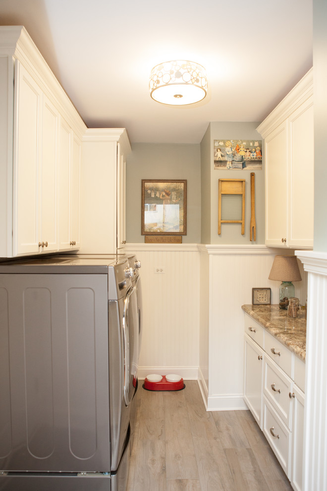 Example of a small classic galley medium tone wood floor dedicated laundry room design in Chicago with recessed-panel cabinets, white cabinets, granite countertops, a side-by-side washer/dryer and gray walls