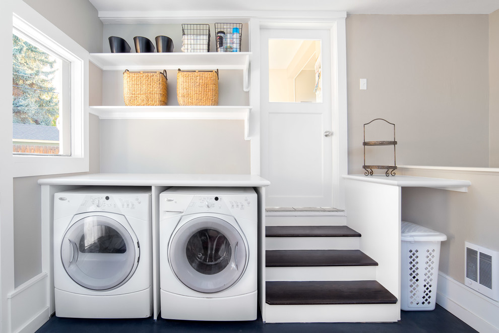 Dedicated laundry room - large transitional concrete floor and black floor dedicated laundry room idea in Boise with white cabinets, laminate countertops, a side-by-side washer/dryer, open cabinets, white countertops and gray walls