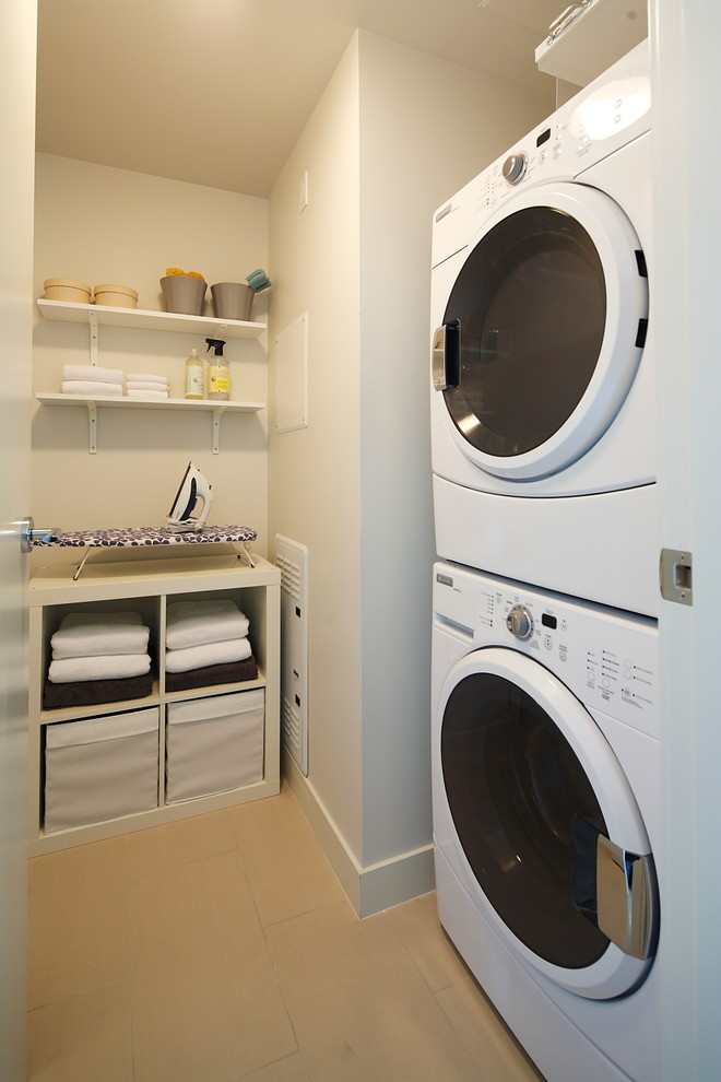Example of a trendy laundry room design in Calgary with a stacked washer/dryer