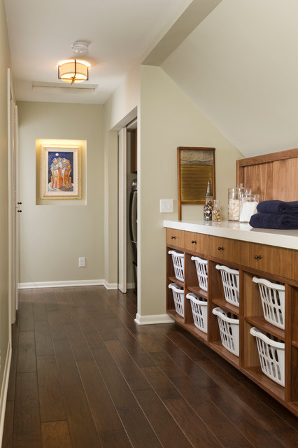 Mid-sized trendy single-wall dark wood floor dedicated laundry room photo in Minneapolis with flat-panel cabinets, medium tone wood cabinets, quartz countertops, gray walls and a concealed washer/dryer