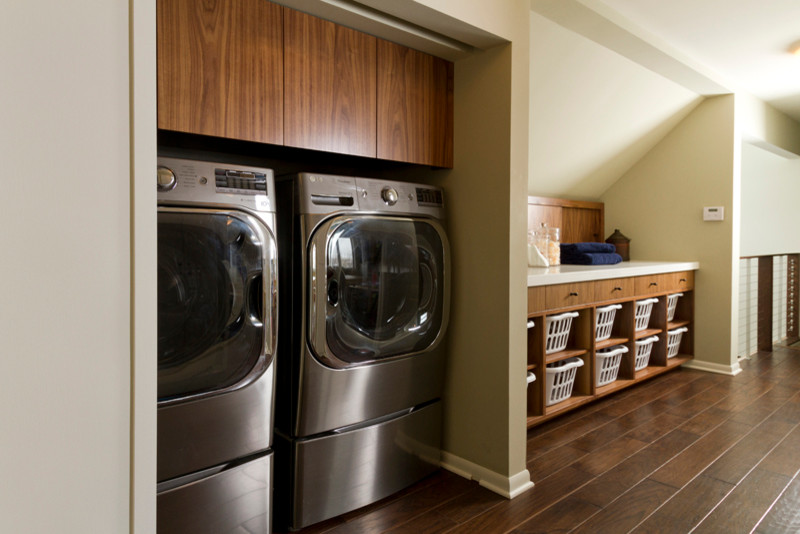 Inspiration for a mid-sized contemporary single-wall dark wood floor dedicated laundry room remodel in Minneapolis with flat-panel cabinets, medium tone wood cabinets, quartz countertops, gray walls and a concealed washer/dryer
