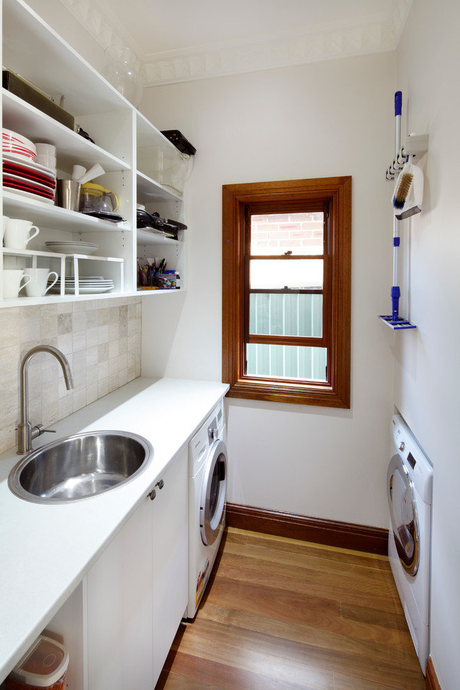 Example of a small classic galley medium tone wood floor utility room design in Sydney with a drop-in sink, flat-panel cabinets, white cabinets, white walls and white countertops