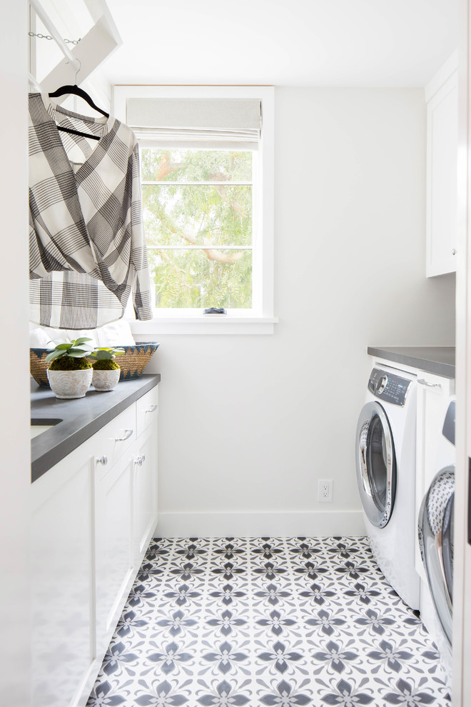 Mid-sized beach style galley gray floor dedicated laundry room photo in Orange County with an undermount sink, shaker cabinets, white cabinets, white walls, a side-by-side washer/dryer and gray countertops