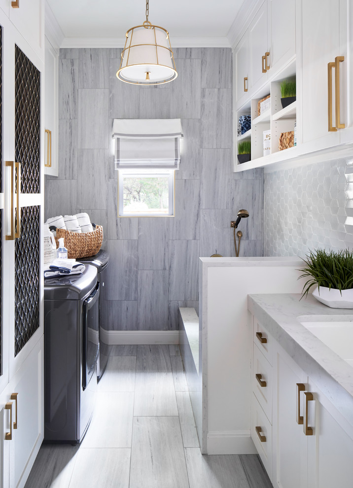 Inspiration for a mid-sized transitional galley gray floor and porcelain tile dedicated laundry room remodel in Austin with an undermount sink, shaker cabinets, white cabinets, a side-by-side washer/dryer, gray countertops, quartz countertops and blue walls