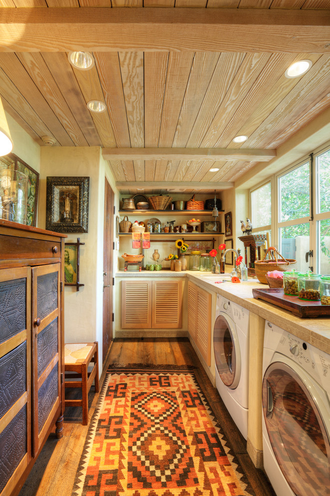 Example of a farmhouse l-shaped utility room design in Sacramento with louvered cabinets and a side-by-side washer/dryer
