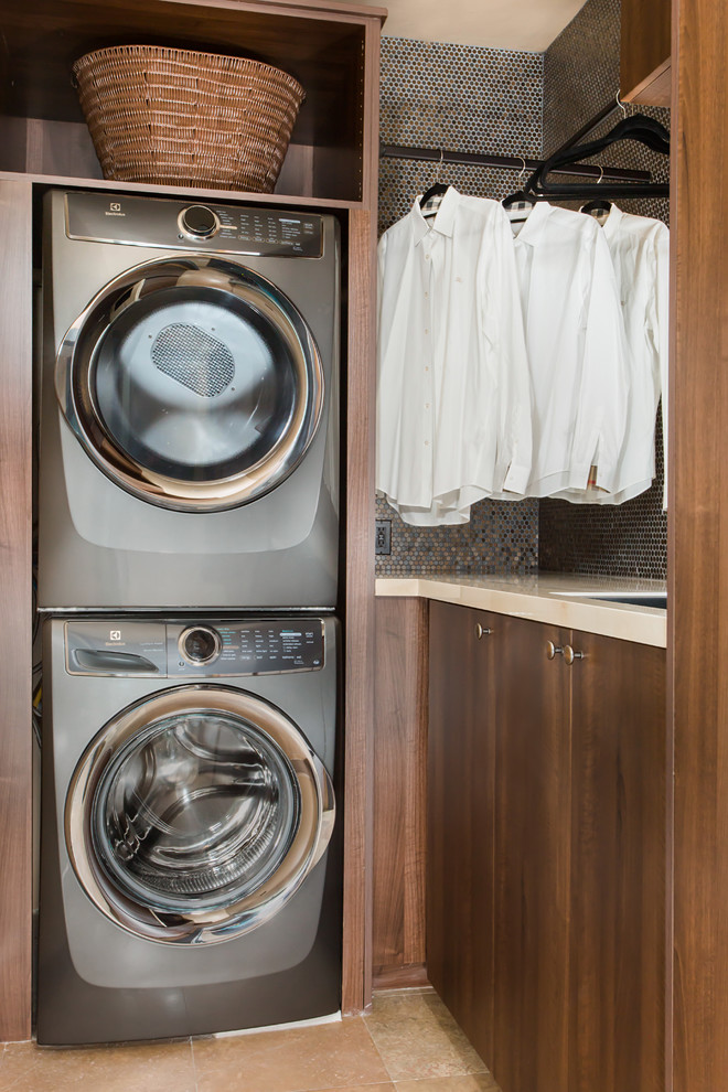 Inspiration for a mid-sized contemporary l-shaped travertine floor and beige floor dedicated laundry room remodel in Los Angeles with an undermount sink, flat-panel cabinets, dark wood cabinets, solid surface countertops, beige walls and a stacked washer/dryer