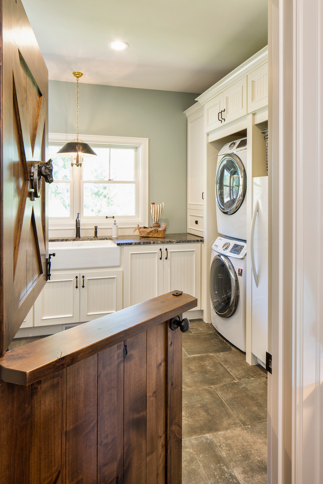 Inspiration for a large farmhouse l-shaped dedicated laundry room remodel in Minneapolis with a farmhouse sink, recessed-panel cabinets, white cabinets, granite countertops, a stacked washer/dryer and gray walls