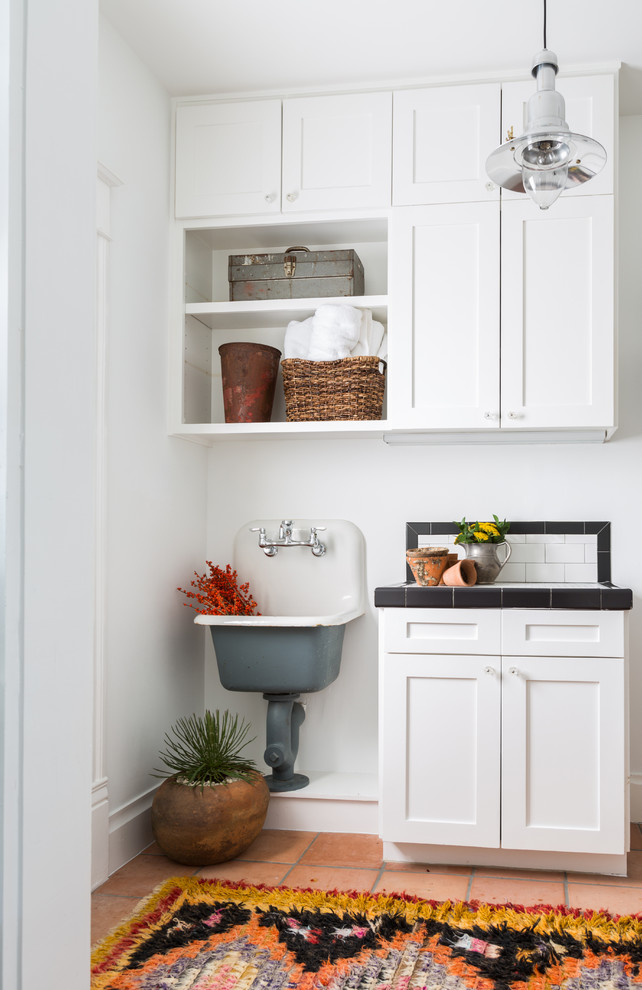 Inspiration for a southwestern terra-cotta tile laundry room remodel in Houston with a single-bowl sink, shaker cabinets, white cabinets, tile countertops and white walls