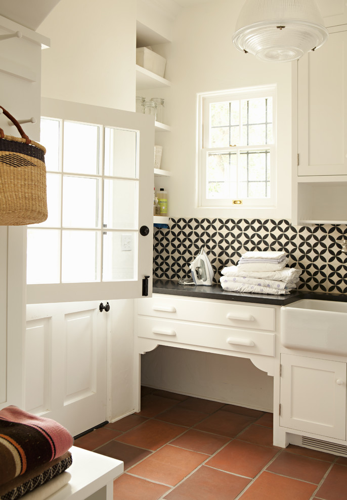 Example of a classic terra-cotta tile and red floor laundry room design in Los Angeles with a farmhouse sink