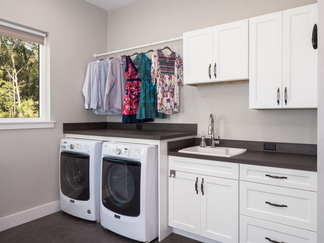 Utility room - mid-sized transitional single-wall dark wood floor and brown floor utility room idea in Miami with a drop-in sink, shaker cabinets, white cabinets, solid surface countertops, white walls, a side-by-side washer/dryer and black countertops