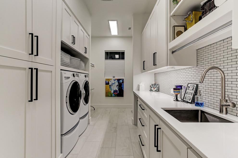 Klassisk inredning av en vita parallell vitt tvättstuga, med en undermonterad diskho, skåp i shakerstil, vita skåp, vita väggar, en tvättmaskin och torktumlare bredvid varandra och grått golv