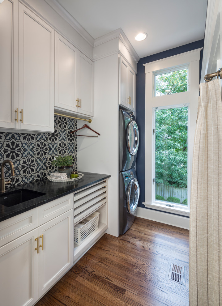 Inspiration for a transitional single-wall dark wood floor and brown floor dedicated laundry room remodel in Cincinnati with an undermount sink, recessed-panel cabinets, white cabinets, blue walls, a stacked washer/dryer and black countertops