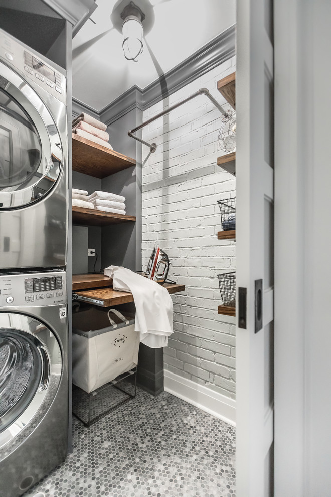 Laundry room - small industrial porcelain tile laundry room idea in Chicago with wood countertops, gray walls, a stacked washer/dryer, open cabinets and brown countertops