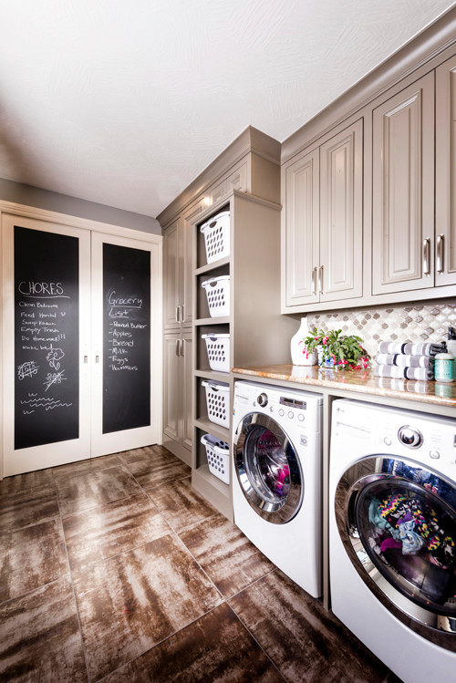 Example of a large transitional galley porcelain tile dedicated laundry room design in Other with gray cabinets, granite countertops, gray walls, a side-by-side washer/dryer and raised-panel cabinets