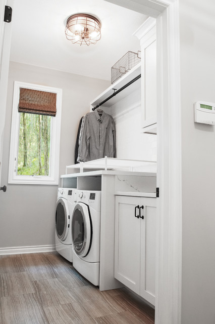 Mid-sized transitional single-wall porcelain floor dedicated laundry room photo in Grand Rapids with a single-bowl sink, shaker cabinets, white cabinets, quartz countertops, gray walls and a side-by-side washer/dryer