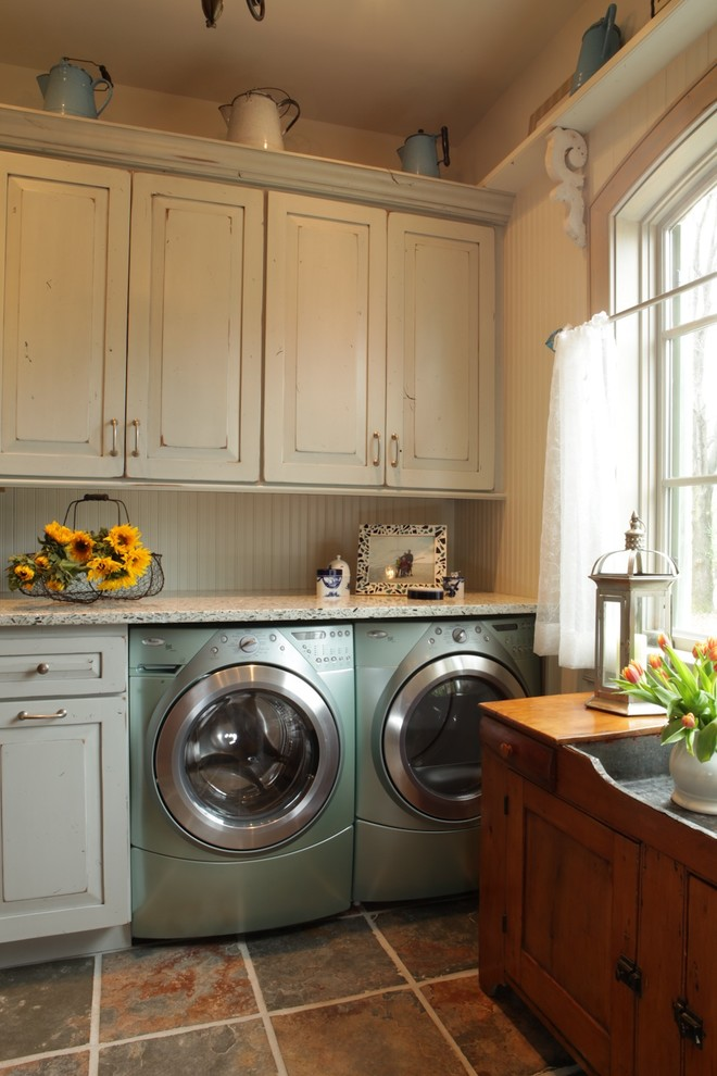 Example of a large classic slate floor utility room design in St Louis with white cabinets, raised-panel cabinets, granite countertops, beige walls and a side-by-side washer/dryer