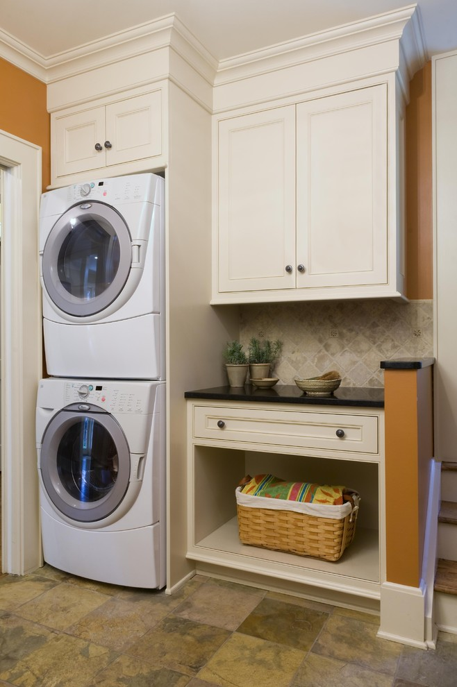 Laundry room - traditional laundry room idea in New York with orange walls and a stacked washer/dryer