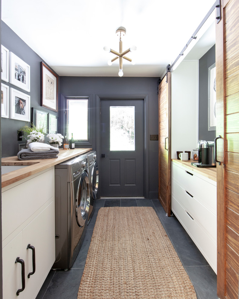Inspiration for a country gray floor and slate floor laundry room remodel in Charlotte with an undermount sink, flat-panel cabinets, wood countertops, gray walls, a side-by-side washer/dryer, beige countertops and white cabinets