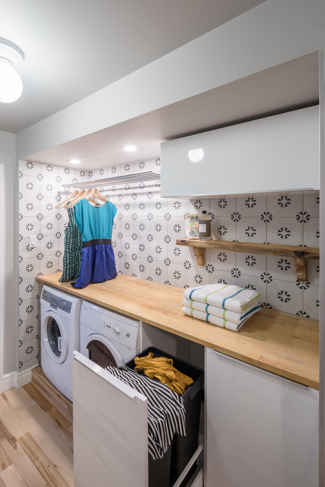 Example of a small trendy single-wall light wood floor dedicated laundry room design in Ottawa with flat-panel cabinets, white cabinets, wood countertops, gray walls, a side-by-side washer/dryer and beige countertops