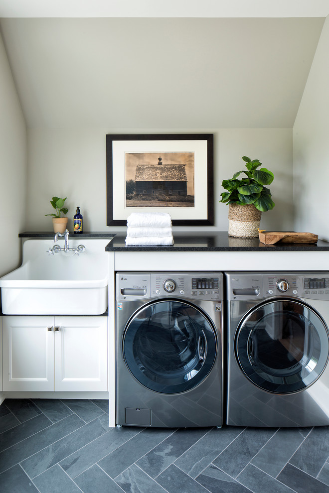 Inspiration for a transitional gray floor dedicated laundry room remodel in Minneapolis with recessed-panel cabinets, white cabinets, a side-by-side washer/dryer, a farmhouse sink, black countertops and gray walls