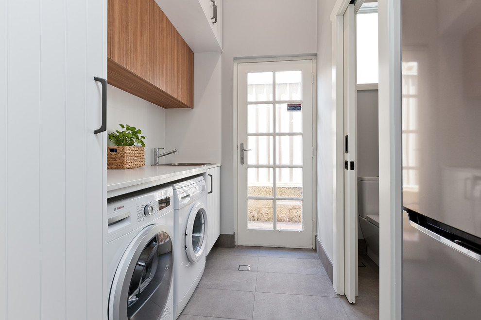 Inspiration for a small contemporary galley dedicated laundry room in Perth with a drop-in sink, white cabinets, quartz benchtops, grey walls, porcelain floors, grey floor, white benchtop and flat-panel cabinets.