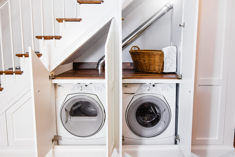 Inspiration for a small timeless medium tone wood floor and brown floor laundry closet remodel in Baltimore with shaker cabinets, white cabinets, wood countertops, a side-by-side washer/dryer and brown countertops