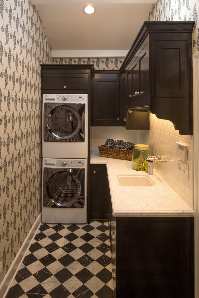 Inspiration for a small timeless l-shaped multicolored floor dedicated laundry room remodel in Los Angeles with black cabinets, a stacked washer/dryer, an undermount sink, shaker cabinets, multicolored walls and white countertops