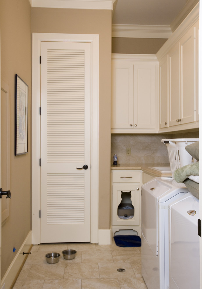 Example of a mid-sized eclectic l-shaped ceramic tile dedicated laundry room design in Houston with a drop-in sink, shaker cabinets, white cabinets, solid surface countertops, beige walls and a side-by-side washer/dryer