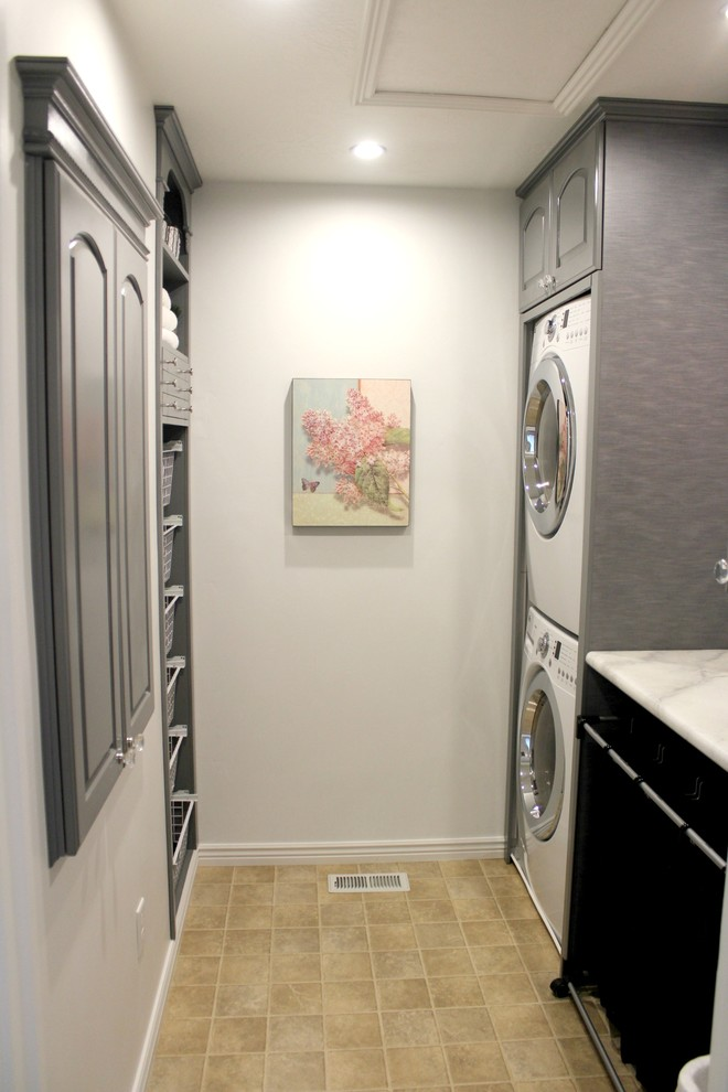 Dedicated laundry room - small transitional galley linoleum floor dedicated laundry room idea in Salt Lake City with raised-panel cabinets, gray cabinets, laminate countertops, white walls and a stacked washer/dryer
