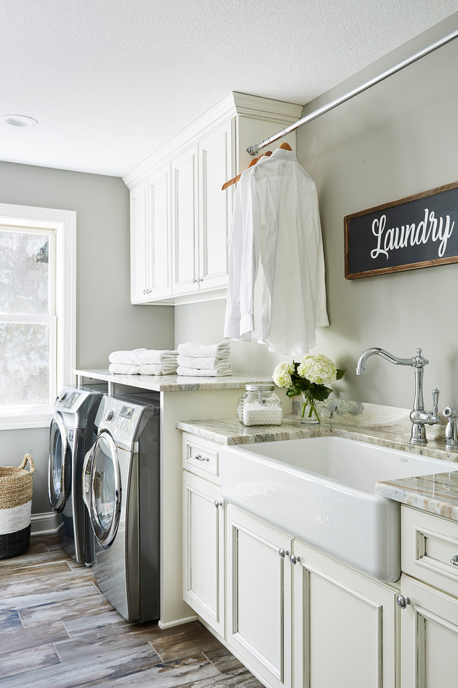 Large elegant single-wall ceramic tile and multicolored floor dedicated laundry room photo in Minneapolis with a farmhouse sink, recessed-panel cabinets, white cabinets, granite countertops, gray walls, a side-by-side washer/dryer and multicolored countertops