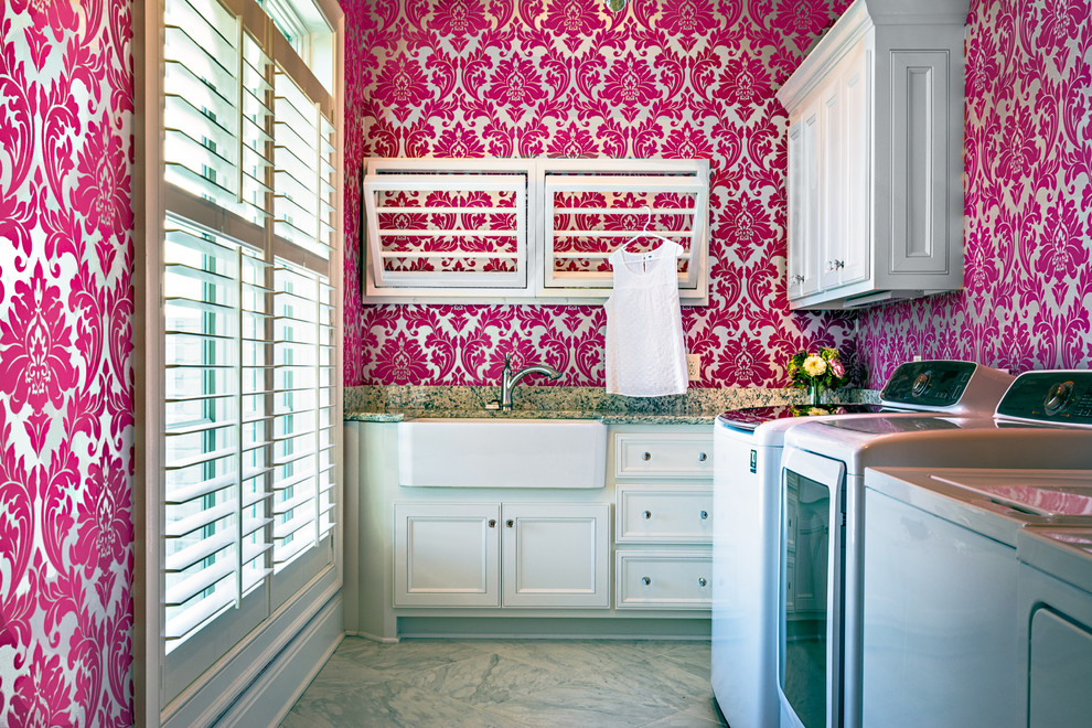 Inspiration for a mid-sized transitional l-shaped utility room remodel in Nashville with a farmhouse sink, recessed-panel cabinets, white cabinets, granite countertops, pink walls and a side-by-side washer/dryer