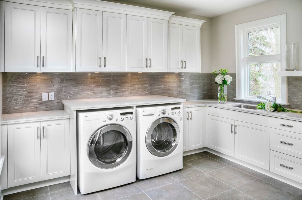 Dedicated laundry room - mid-sized transitional l-shaped ceramic tile dedicated laundry room idea in Toronto with an undermount sink, shaker cabinets, white cabinets, granite countertops, gray walls and a side-by-side washer/dryer