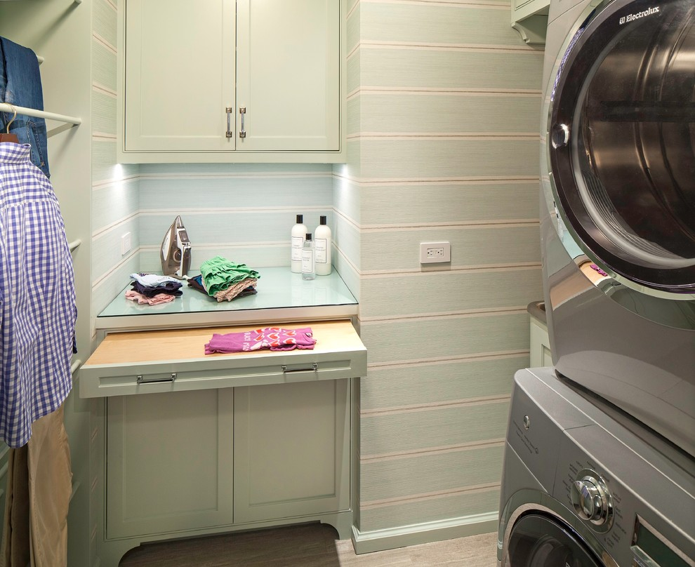 Example of a small transitional ceramic floor dedicated laundry room design in New York with an utility sink, green cabinets, glass countertops, green walls and a stacked washer/dryer