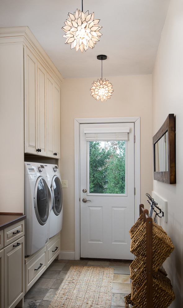 Example of a country slate floor laundry room design in Cincinnati with wood countertops, beige cabinets and raised-panel cabinets